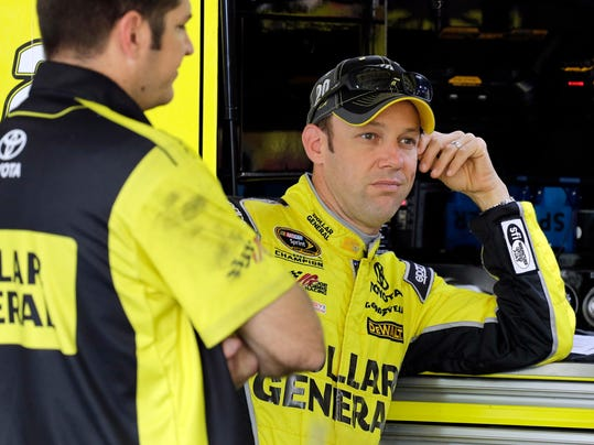 Matt Kenseth, right, talks to crew members before practice for the NASCAR Sprint Cup series auto race in Concord, N.C., Thursday, Oct. 8, 2015. (AP Photo/Terry Renna)