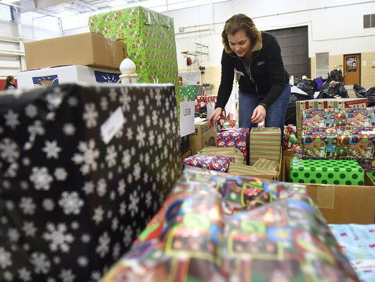 Volunteer Susan Pauly prepares gifts for distribution
