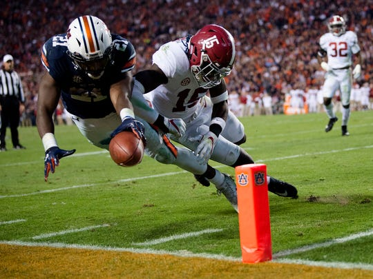 Auburn running back Kerryon Johnson (21) dives for the end zone as Alabama defensive back Ronnie Harrison (15) knocks him out of bounds during the Iron Bowl on Saturday, Nov. 25, 2017, in Auburn, Ala.