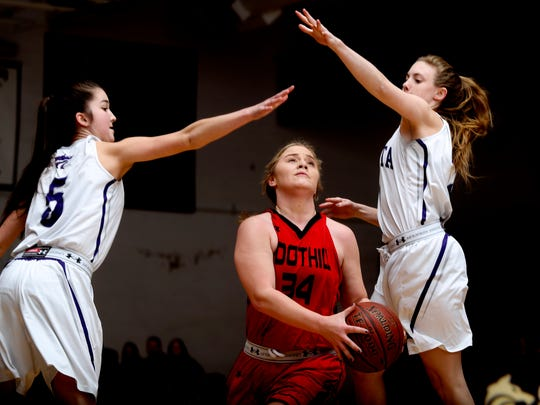 Foothill's Riley Wallen takes the ball to the hoop between Shasta's Ava Jackson, left, and Grace Woods, right, Thursday during the Cougars' 40-38 playoff win over the Wolves.