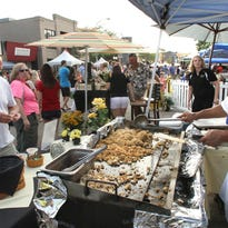 Chef Matthieu Nguyen serves up shrimp fried rice and other Sagano favorites during the 2014 Taste of Brighton. At left is Bill Gibson of Florida, a former Livingston County resident.