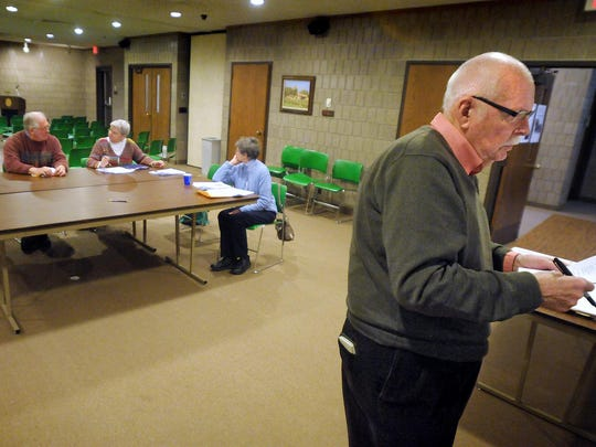 Bill Morgan, right, casts a vote at a Stearns History Museum event in February 2012. Museum staff say his research as an architectural historian has left a rich documentation that the area otherwise would not have.