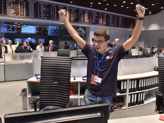 The picture released by the European Space Agency ESA on Wednesday, Nov. 12, 2014, a scientist reacts in the main control room at the European Space Agency after the first unmanned spacecraft Philae landed on the comet called 67P/Churyumov-Gerasimenko, at the control centre in Darmstadt, Germany, Wednesday, Nov. 12, 2014. Europe's Rosetta space probe was launched in 2004 with the aim of studying the comet and learning more about the origins of the universe.