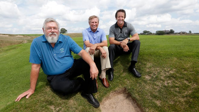 The three architects of Erin Hills, from left, Ron Whitten, Michael Hurdzan and Dana Fry, sit next to a bunker on the ninth hole of the golf course.