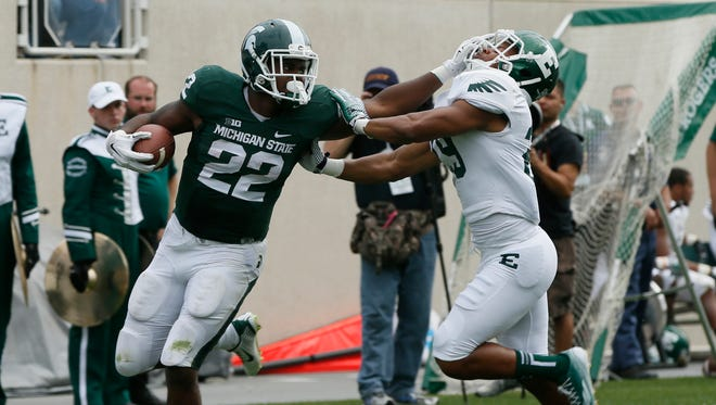 Michigan State's running back Delton Williams stiff arms Eastern Michigan's Jalen Williams to complete his run to the end zone on an 80 yard touchdown run in the fourth quarter of their 73-14 win over Eastern in East Lansing on Saturday, September 20, 2014.