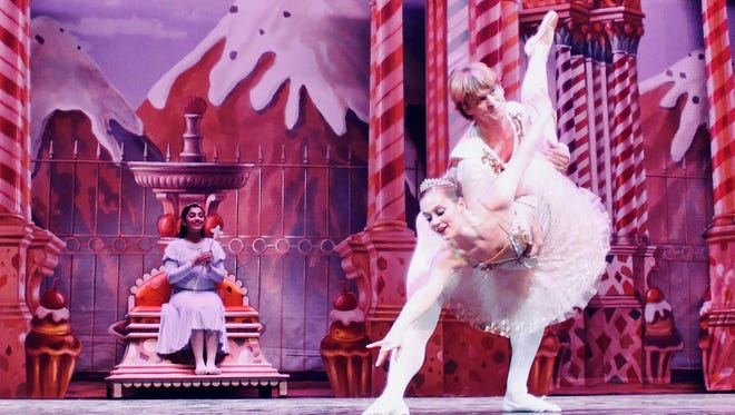 """The Cavaliere, danced by guest artist David Sanders, performs with the Sugar Plum (Ashlen Loskot) as Clara (Manasvi Reddy) looks on in the background during a dress rehearsal of the Wichita Falls Ballet Theatre's """"The Nutcracker."""""""