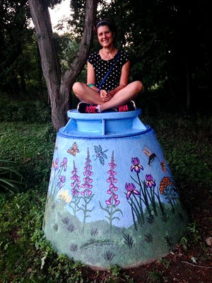 Denise Birmingham sits atop the manhole cover that she painted in a beautification effort for the Town of Clinton.