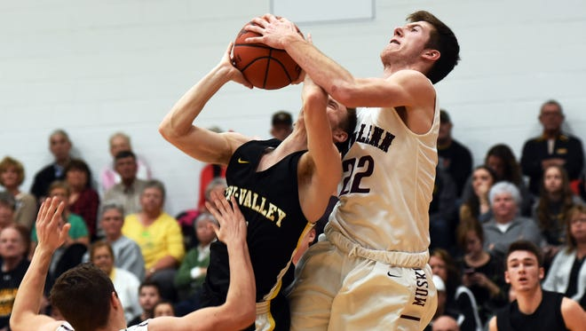 Josh Raley ties up Tri-Valley's Cam Mercer during a drive to the basket in the second half of John Glenn's 61-44 win on Tuesday night in New Concord. The Muskies jumped into a tie with the Scotties for the Muskingum Valley League lead.