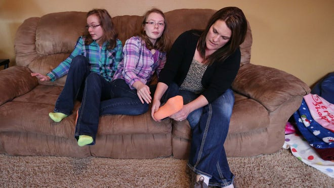 Kim Novy fixes her daughter Lindsey's sock, with Lindsey's twin sister Lauren by her side on Monday, Jan. 19, 2015 in their home in Altoona. The twins both have a severe form of epilepsy.