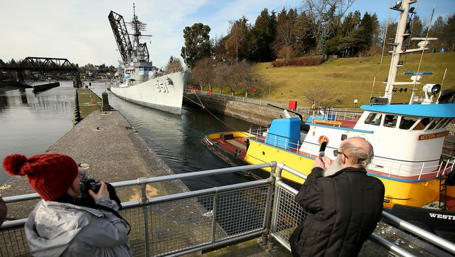 Spectators snap photos Thursday as the Western Navigator tug tows the USS Turner Joy into the Hiram M. Chittenden Locks in Ballard .