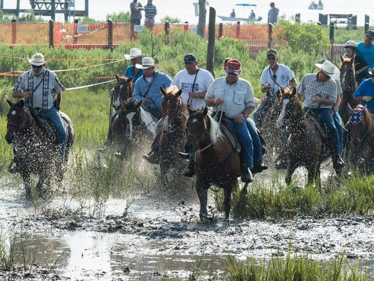 Saltwater Cowboys make their way through the mud after