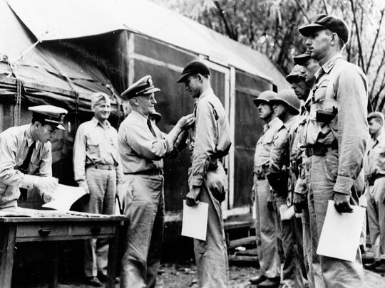 Adm. Chester W. Nimitz, the Commander in Chief of the U.S. Pacific Fleet, awards the Navy Cross to Marine fighter pilot Capt. Marion Carl during a visit to Guadalcanal in 1942.