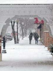 People walk through snow Friday on Main Street  in
