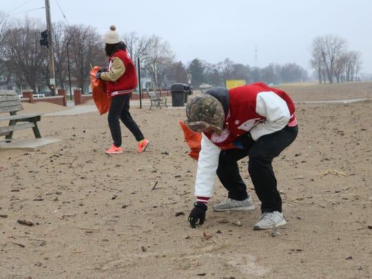 Port Clinton High School students Erin Hiller and Nikolas Skoufos volunteer their Saturday morning to help clean up the city beach, despite heavy rain, strong winds and morning temperatures in the high 30s.