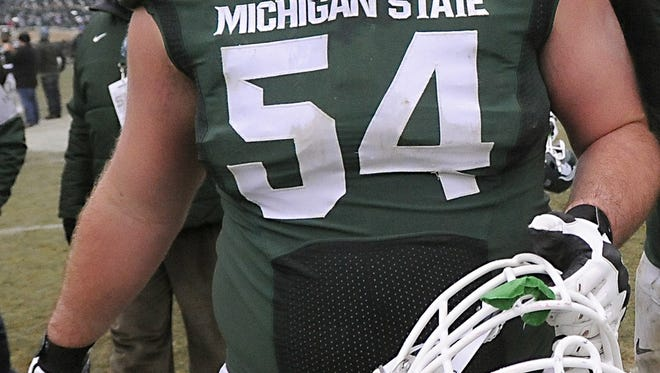 MSU senior lineman Connor Kruse, left, celebrates with teammate Donavon Clark after his last home game and  MSU's 45-3 win over Rutgers in East Lansing on 11/22/2014.