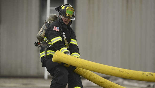 Green Bay Fire Department recruit Matt Gilanyl straightens out a hose while working on a skills demonstration at the NWTC Public Safety Training Center in Green Bay on Friday, May 15, 2015.