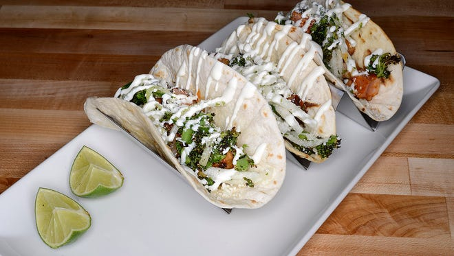 Pork Belly Tacos: grilled flour tortilla, chili glaze, cucumber, jicama, charred kale and cotija at 1919 Kitchen & Tap at Lambeau Field.