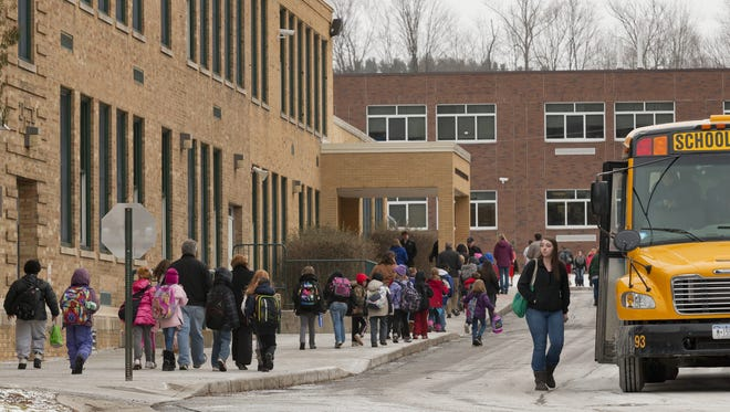 Newfield students leave the elementary school, left, and combined middle and high school building, background, in a file photo from 2013.