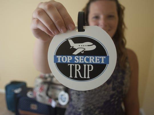 Katie Miller shows a logo of her business Top Secret Trip.