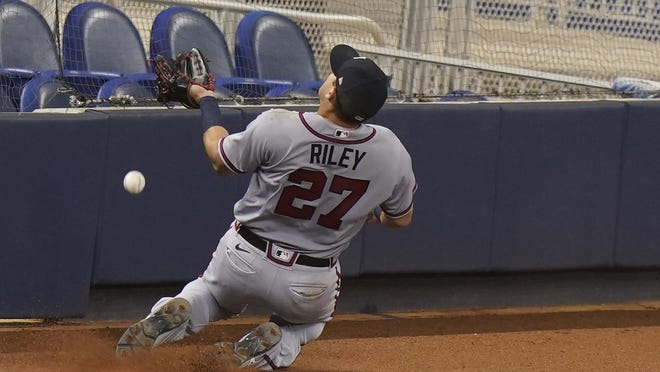 Atlanta's Austin Riley is unable to make a sliding catch in foul territory during Friday's game against the Marlins.