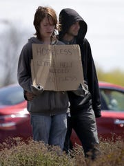 A couple holds a sign Monday at the intersection of