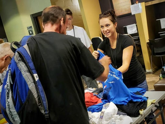 Room in the Inn volunteers and interns give out T-shirts to homeless clients.