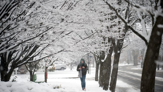 Heavy snow falls as Treshaun Adams walks along Collings Avenue in Collingswood during a previous storm. Snow is expected again today in parts of South Jersey.