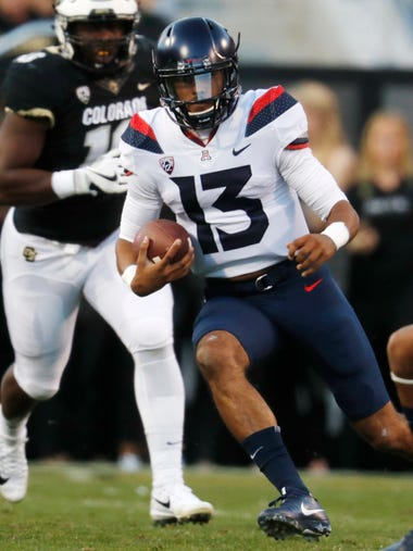 Arizona quarterback Brandon Dawkins, front, slips past
