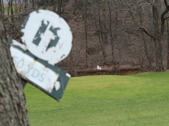 A tee marker sticks out from a tree at the 11th hole
