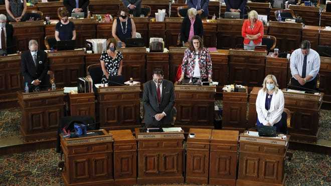 State Representatives stand at their desks during the opening prayer in the Iowa House chambers, Wednesday, June 3, 2020, at the Statehouse in Des Moines, Iowa. Lawmakers returned Wednesday after suspending the session when the coronavirus pandemic surfaced in Iowa in March, prompting state officials to close the state Capitol.