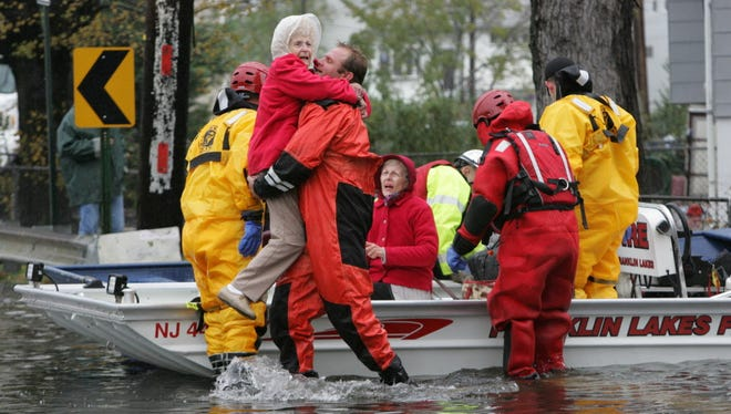 A rescue worker carries an elderly woman to dry ground in Little Ferry after rescuing her from her home Tuesday morning, Oct. 30, 2012.