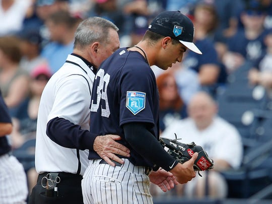New York Yankees second baseman Tyler Wade is taken to the locker room after injuring his hand while diving for a ball during the sixth inning against the New York Mets at George M. Steinbrenner Field on March 11, 2018.