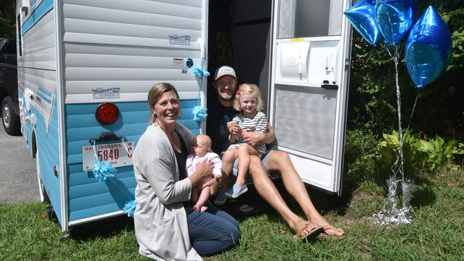 Addison Marshall, right, with her parents, Patrick and Meg Marshall, and her baby sister, Emmy, received a camper trailer from the Make-A-Wish Foundation on Friday. The camper resembles one featured in stories of Peppa Pig, one of Addie's favorite characters.