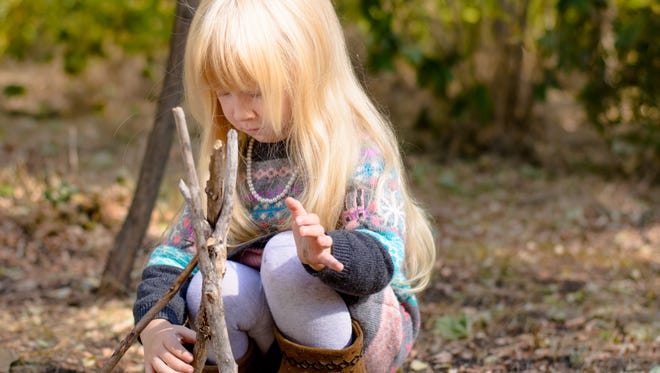 Girl Assembling Sticks on the Ground at the Woods.