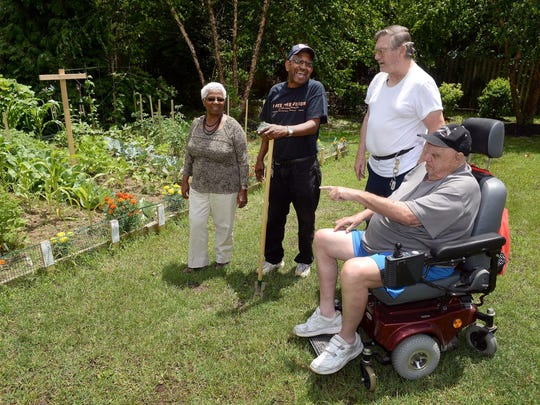 Buena Gardens residents Elaine and Larry Gray, Richard Loveland and Vince Nicolo, talk beside the senior garden they organized for their community at Buena Gardens in Minotola on Monday.