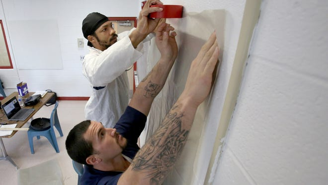 (L to R) Robert Ballinger, 36 of Detroit tapes down plastic over a door frame as Matthew Hernandez, 33 of Detroit holds it in place during a lead abatement exercise at the Detroit Reentry Center on Ryan Road in Detroit on Saturday, Jan. 7, 2017.