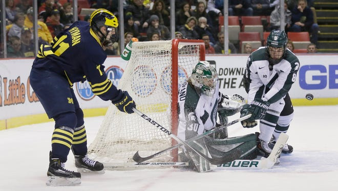 Michigan State goalie Jake Hildebrand (30) and defenseman Josh Jacobs deflect a shot by Michigan forward Zach Hyman during the first period Jan. 30, 2015 in Detroit.