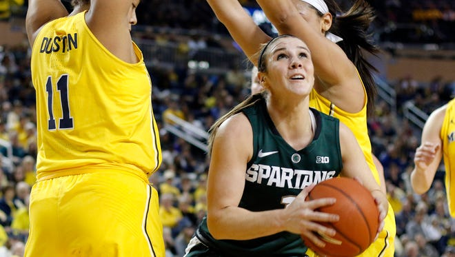 Michigan State's Tori Jankoska squeezes between Michigan's Jillian Dunston, left, and Kysre Gondrezick, right, for a shot Sunday, Feb. 19, 2017, at the Crisler Center in Ann Arbor, Mich. Michigan State won 86-68.