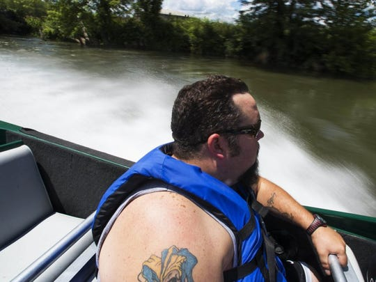 Patrick Moore watches the French Broad River flash by while riding a jet boat Thursday, Aug. 11, 2016, in Sevierville.