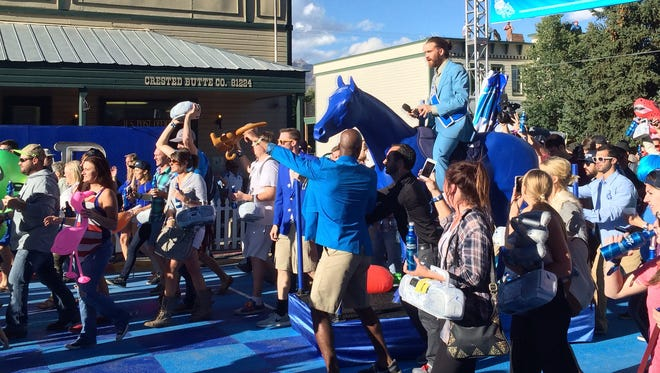 """Revelers at """"Whatever, USA"""" parade down Elk Avenue in Crested Butte, Colo., on Friday, Sept. 5, 2014, led by the fake town's """"mayor,"""" who stars in Bud Light commercials. The brewer plans to take over another town in 2015 for its advertising campaign."""