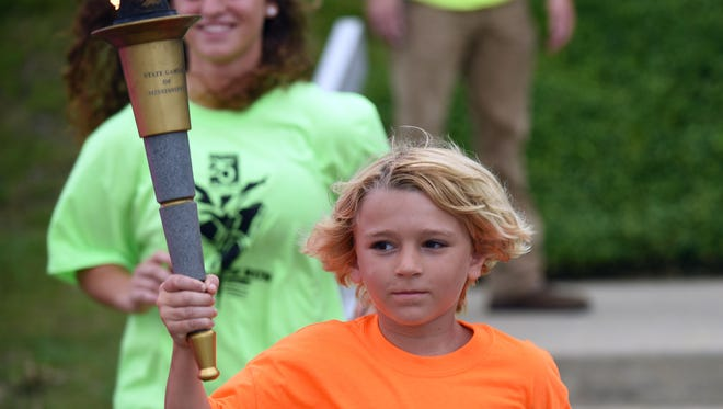 Dallas  and Christie Stricker run with the State Games of Mississippi torch through Hattiesburg on Wednesday. The  State Games of Mississippi is celebrating their 25th year.