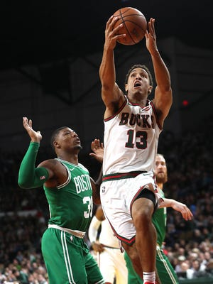"""Bucks guard Malcolm Brogdon drives for a layup against Celtics guard Marcus Smart during the """"Return to the MECCA"""" game on Thursday night."""