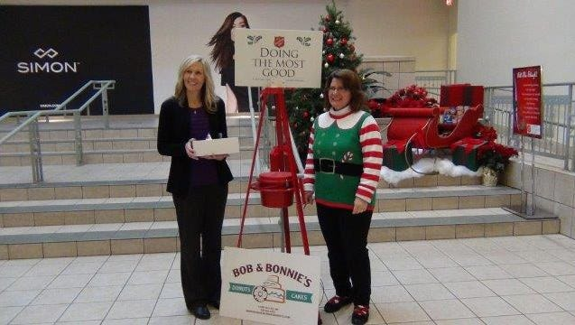 """Sunny 97-7 and The Salvation Army delivered Bob and Bonnie's Donuts and spread Christmas cheer to businesses """"doing the most good"""" in the community. Here, Tracy Vassallo, Simon Forest Mall Manager, accepts a delivery from Connie Millard, The Salvation Army Community Resource Development Director."""