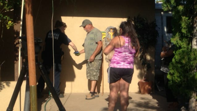 Vanessa Ruiz, 13, (at right) holds one of the family dogs that was sickened Thursday and looks on as her father gives an Arizona Humane Society employee a sample of dog food. Eight of the family's 12 chihuahuas died and the others were sickened. Police think someone may have poisoned them.