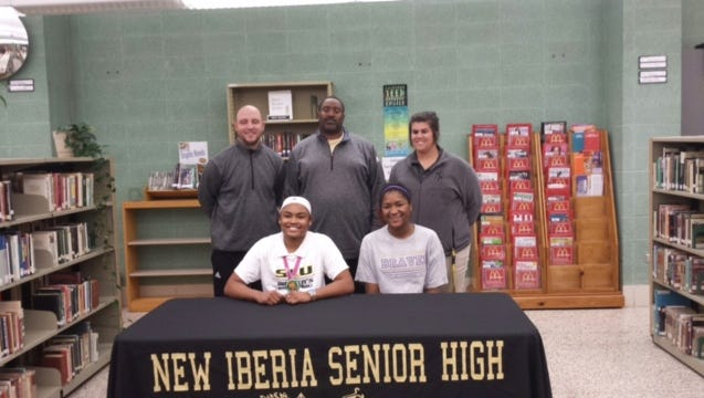 New Iberia's Morgan Carrier, left, and Jamaysha Bernard, right, sign their letters of intent Wednesday.