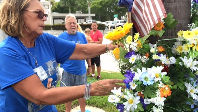 Tracy Miller, the mother of Adam King, who was killed in a hit-and-run motorcycle crash a year ago Monday, places flowers at a memorial for her 18-year-old son.