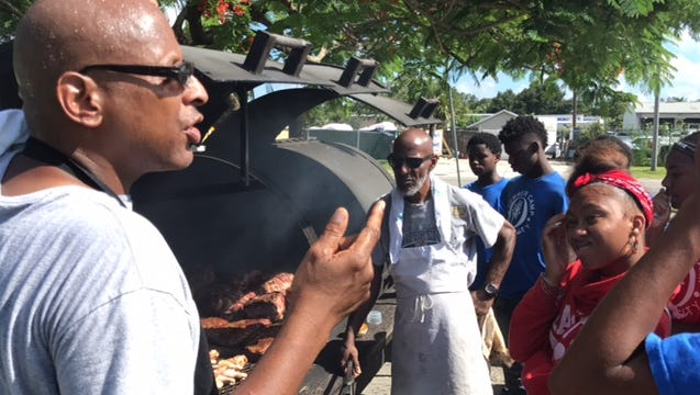 Mark Anderson, manager at the Farmer's Market on Edison Avenue, explains barbecuing to teens in The Quality Life Center's summer life skills program.