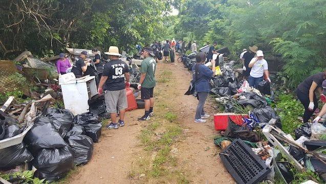 Volunteers clean up an illegal dumpsite in Dededo in a Basta I Basula event Saturday,
