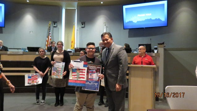First place Veterans Day poster contest winner Cruz Larez's receives a framed copy of his art work from Mayor Ken Miyagishima at the City Council meeting on Oct. 16, where all the finalists were recognized. His poster will be used as the official Las Cruces Veterans Day Parade poster and Cruz and his grandfather, Vietnam War veteran Paul H. Gonzales, will be participating in the parade as well.