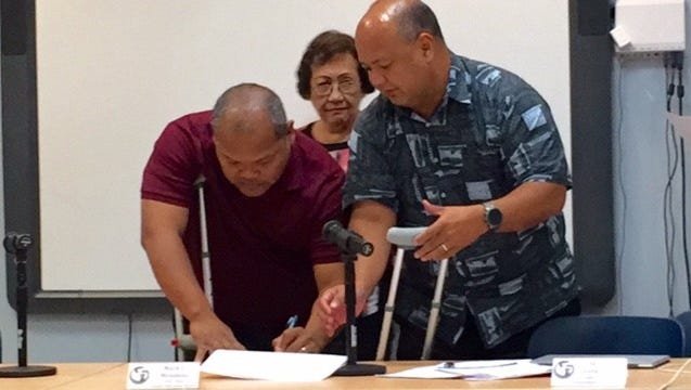 Guam Education Board Chairman Mark Mendiola, left, signs the newly adopted proposed fiscal 2019 budget of nearly $334.9 million for the Guam Department of Education, while Superintendent Jon Fernandez and vice chairwoman Maria Gutierrez look on, Friday night in Tiyan. The proposed Guam DOE budget, which got a 7-0 vote, is $97.5 million more than the current year's appropriation, and is subject to reduced allotment because of the government of Guam's projected $66 million shortfall for 2019.